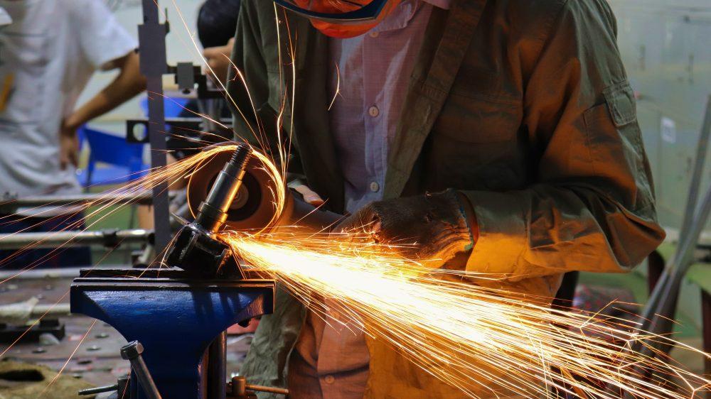Man cutting iron - Photo by Xi Wang on Unsplash