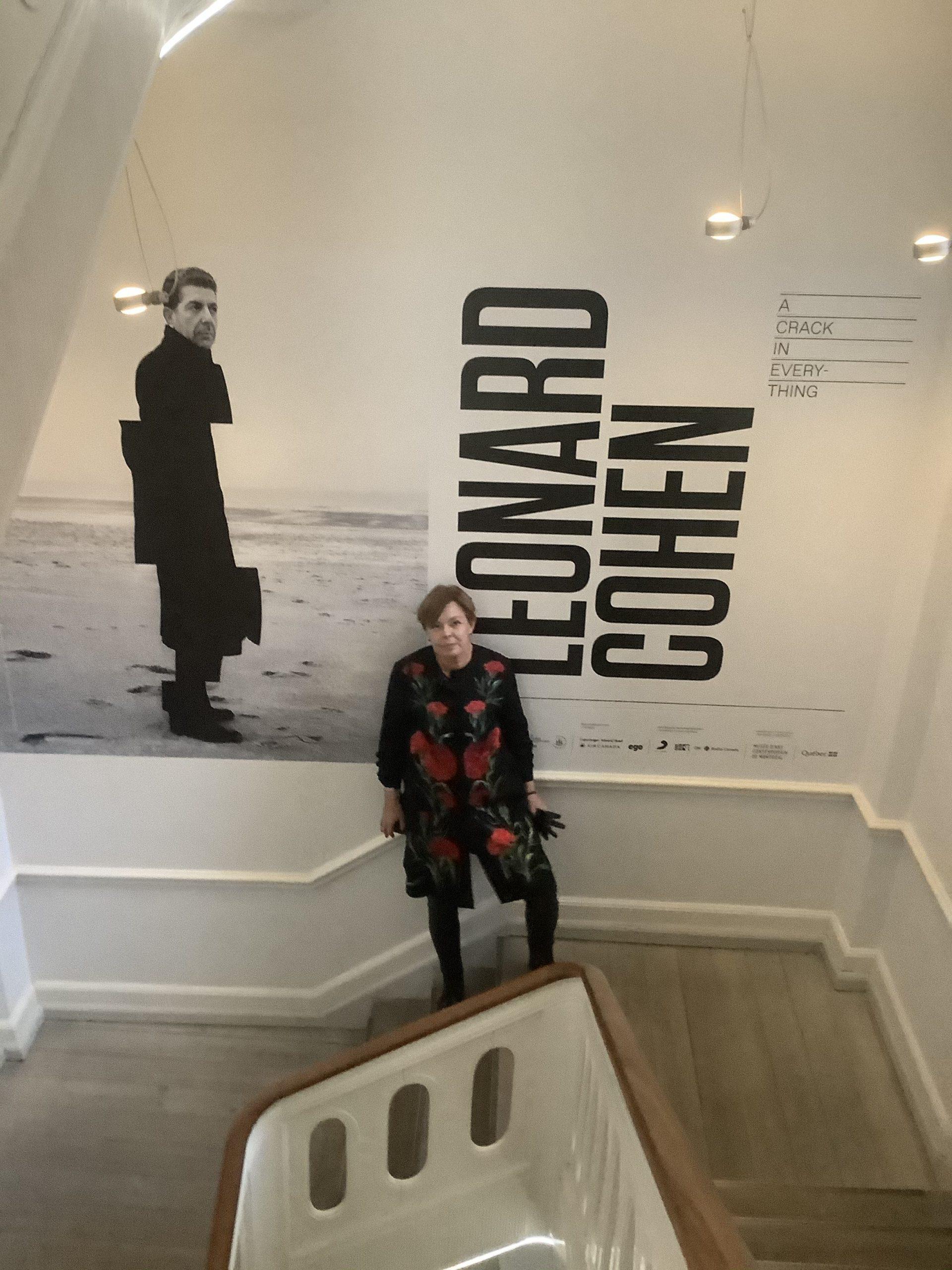 Eva Kofod-Hansen på trappen ved Gl. Strand med Leonard Cohen-plakat som baggrund
